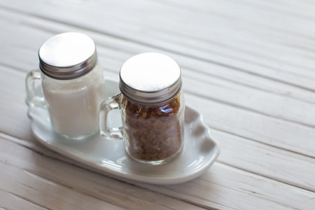 sweetening: Brown sugar in the bottles on wooden table. Stock Photo