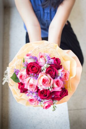 Woman hands showing  roses bouquet flowers. photo