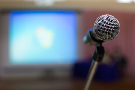 Microphone in concert hall or conference room with defocused bokeh lights in background photo