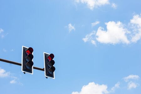 green street sign: Traffic lights on blue sky background.