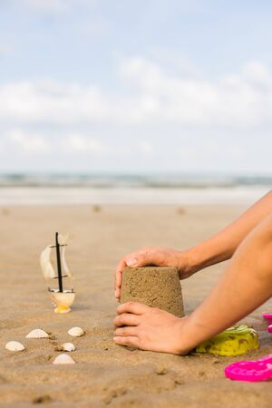 Making a Sand Castle at the beach summer concept