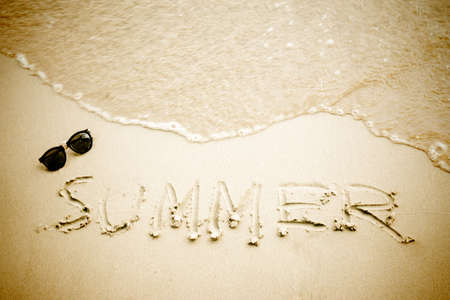 Summer word and sunglasses on sandy beach, vintage natural background.