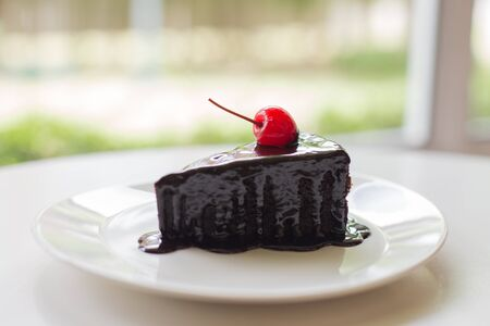 indulgence: Chocolate Cake with cherry, soft focus. Stock Photo