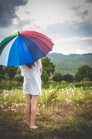 Outdoor portrait of asian girl waiting for some one with rainbow colours umbrella vintage and retro tone, soft focus.
