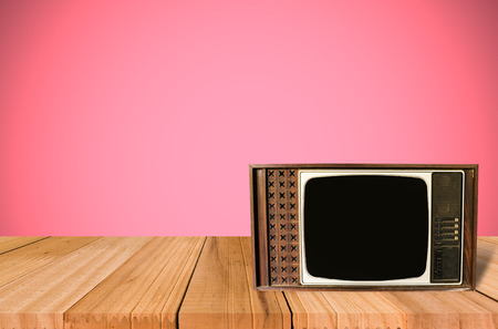 retro tv: Old Style Photo. Classic vintage and retro TV on the table with pink wall background. Stock Photo