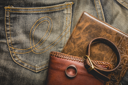 brown leather hat: still life photography : Brown leather wallet, Leather wristbands, silver ring and adventure hat on jeans background,  men casual concept, vintage and retro style.