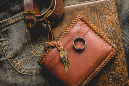 brown leather: still life photography : Brown leather wallet, Leather wristbands, silver ring and adventure hat on jeans background,  men casual concept, vintage and retro style.