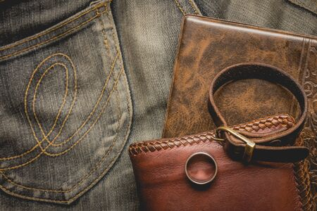 still life photography : Brown leather wallet, Leather wristbands, silver ring and adventure hat on jeans background,  men casual concept, vintage and retro style.