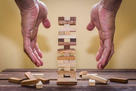 fragile economy: Planning, risk and strategy in business, businessman gambling placing wooden block on a tower