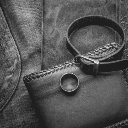 wristbands: still life photography : Brown leather wallet, Leather wristbands, silver ring and adventure hat on jeans background,  men casual concept, vintage and retro style.