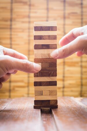 fragile economy: Planning, risk and strategy in business, businessman gambling placing wooden block on a tower.