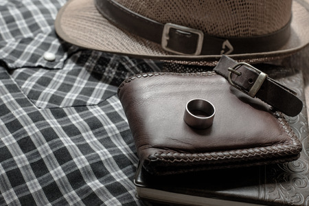 wristbands: still life photography : Brown leather wallet, Leather wristbands, silver ring and adventure hat on jeans background, men casual concept, vintage and retro style Stock Photo