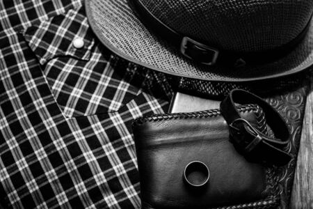 brown leather hat: still life photography : Brown leather wallet, Leather wristbands, silver ring and adventure hat on jeans background, men casual concept, vintage and retro style Stock Photo