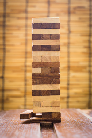 Planning, risk and strategy in business, businessman gambling placing wooden block on a tower.
