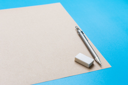 room for your text: A white note book with lots of room for your text or image and a regular pencil and rubber on a wooden desk.