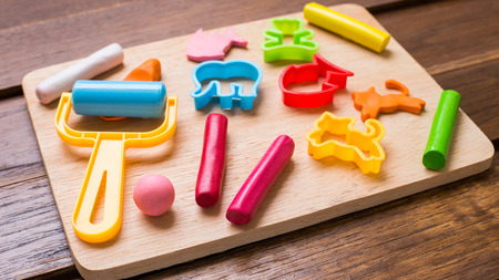Plasticine and tools are on wooden background. Stock Photo