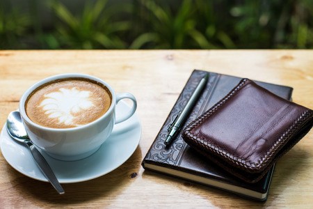 capacino: hot coffee with abstract shape latte art placed near leather cover notebook on wooden table.