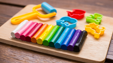 plasticine: Plasticine and tools are on wooden background. Stock Photo