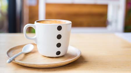 木製のテーブルの上にカップでアート ラテ コーヒー。