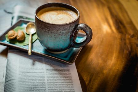 capuchino: café latte arte caliente con el periódico en la mesa de madera, vintage y retro.