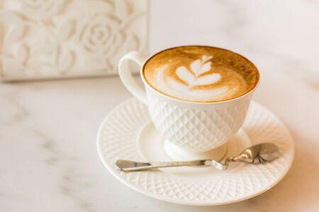 Heißer Kunst Latte Kaffee in einer Schale auf Holztisch. Standard-Bild