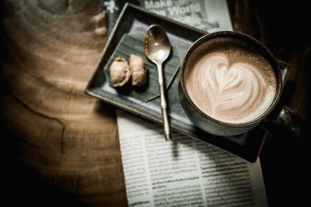 energizing: hot latte art coffee with newspaper on wooden table, vintage and retro style.