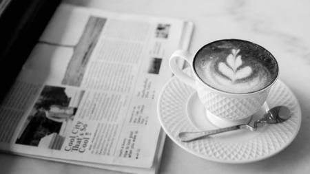 木製のテーブル、ヴィンテージやレトロなスタイルの新聞とコーヒー ホット ラテアート