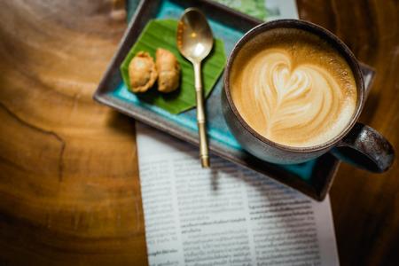 hete latte kunstkoffie met krant op houten lijst, uitstekende en retro stijl.