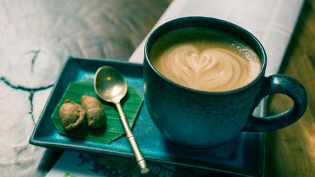 hete latte art koffie met krant op houten tafel, vintage en retro stijl.
