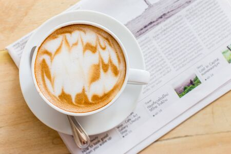 Hot latte art coffee cup with newspaper on wooden table, vintage and retro style