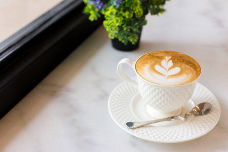 taza de café: Arte caliente Latte Café en una taza en la mesa de madera. Foto de archivo