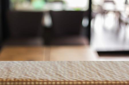 tela blanca: cuadros cuadro de tela en la mesa vacía y restaurante o cafetería para su fotomontaje o exposición del producto.