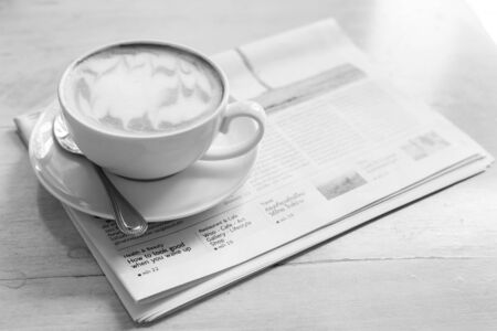 Hot latte art coffee cup with newspaper on wooden table, vintage and retro style, black and white tone