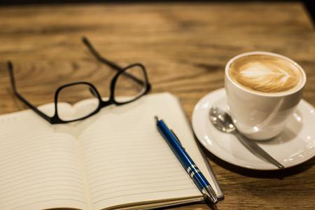 木製テーブルとメモ帳、ヴィンテージやレトロ スタイルに熱いラテ アート コーヒー カップ。
