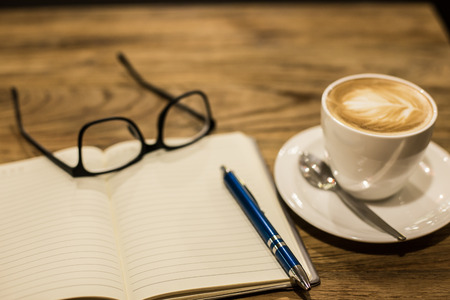 coffee meeting: Hot latte art coffee cup on wooden table and note book, vintage and retro style. Stock Photo