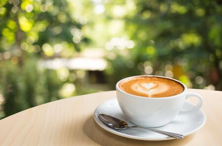 decaffeinated: Coffee cup with hot coffee on old wood table in blur green nature background for product display montage.