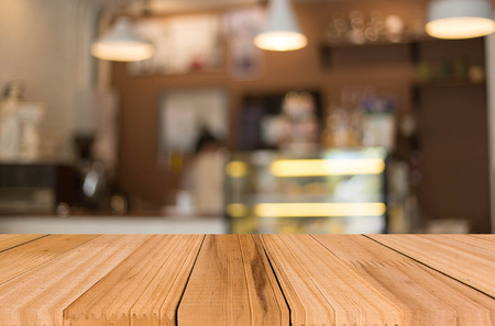 dining room: Selected focus empty brown wooden table and Coffee shop blur background with bokeh image, for product display montage.