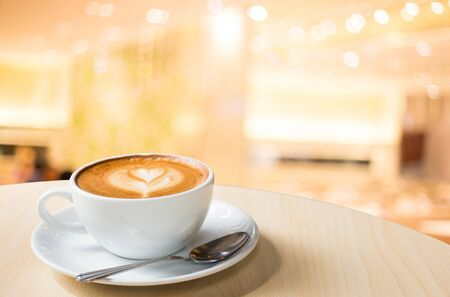 Hot art Latte Coffee in a cup on wooden table and Coffee shop blur background with bokeh image Stok Fotoğraf