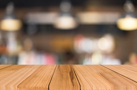 backdrop design: Selected focus empty brown wooden table and Coffee shop blur background with bokeh image for your photomontage or product display.