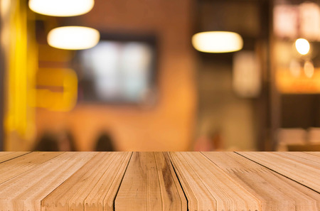 old desk: Selected focus empty brown wooden table and Coffee shop blur background with bokeh image, for product display montage.