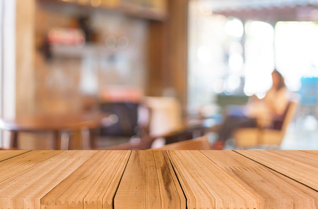 Selected focus empty brown wooden table and Coffee shop blur background with bokeh image Standard-Bild