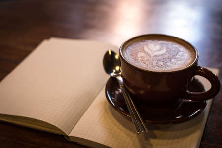 vintage leaf: Coffee cup and notebook on grunge background.
