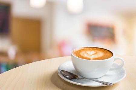 熱いアートとコーヒーの木のテーブルの上にカップでラテのコーヒーは、ピンぼけ画像で背景をぼかし。