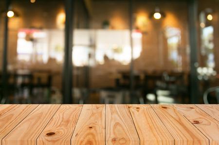 選択したフォーカス空茶色の木製のテーブルとコーヒー ショップは、ピンぼけ画像で背景をぼかし。