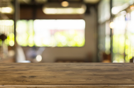 focus on background: Selected focus empty brown wooden table and Coffee shop blur background with bokeh image, for product display montage.