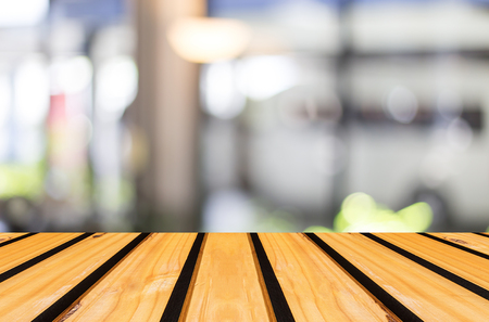 room background: Selected focus empty brown wooden table and Coffee shop blur background with bokeh image.