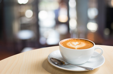 Hot art Latte Coffee in a cup on wooden table and Coffee shop blur background with bokeh image 스톡 콘텐츠