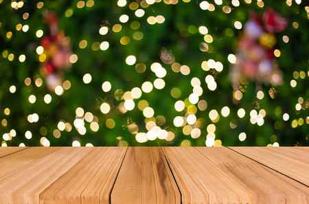 colorful light display: Christmas holiday background with empty wooden deck table over festive bokeh. Ready for product montage.