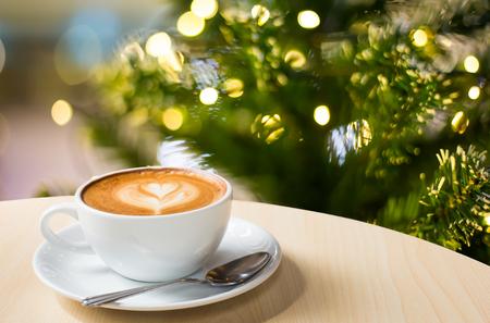 tazas de cafe: Foto de la hermosa luz de Navidad festiva, la taza de caf� con leche en la mesa de madera sobre fondo bokeh Foto de archivo