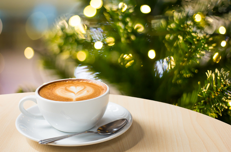 Photo of beautiful Christmas light festive, white coffee cup on the wooden table on bokeh background